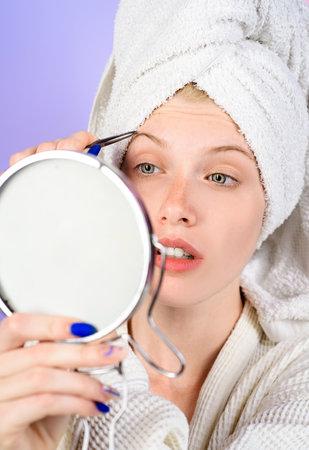 Epilate eyebrows. Girl pluck eye brow looking in mirror. Woman with tweezers. Beauty care. Correction procedure in beauty salon.