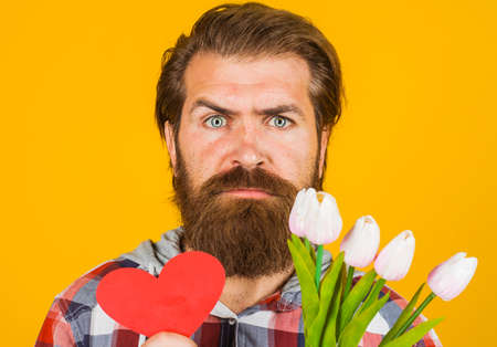 Valentines Day. Serious man with red heart and flowers. Valentine presents with love. 版權商用圖片