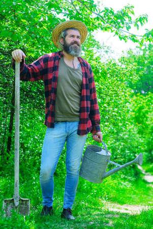 Farm. Smiling man with watering can and shovel. Farmer preparing to planting. Gardening. Garden spade. 版權商用圖片