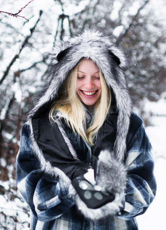 Winter girl in fur hat and jacket. Beautiful woman in winter park. Wintertime. Cold weather.
