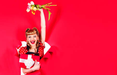 Smiling retro woman with flowers and gift. Pinup girl. Pin up girl with tulips and gift. 版權商用圖片