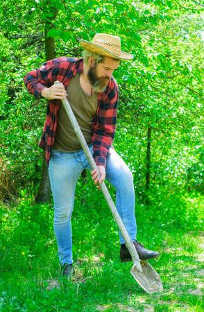 Man with shovel in garden. Eco-farm. Male with gardening tools. Gardener work.