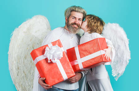 Happy father with little son in angel costumes with gifts. Valentines angels.