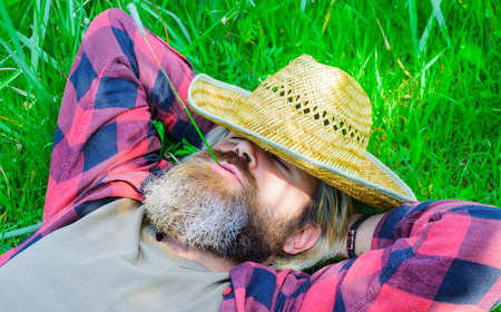 Happy relaxed male in checkered shirt and hat lying on green grass. Happy man relaxing outdoors in summer.