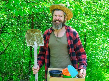 Professional gardener. Happy bearded man in garden. Eco-farm. Male with gardening tools. 版權商用圖片