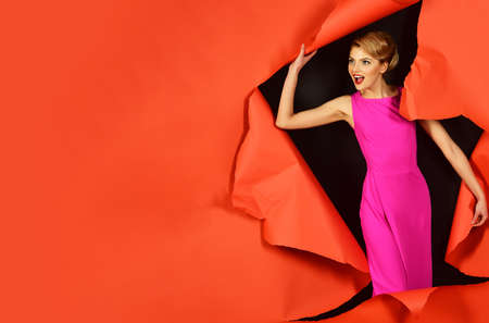 Surprised girl in pink dress. Sexy woman with perfect makeup, red lips breaking paper background. Copy space for advertise.