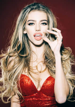 Sexy Woman putting transparent retainer in teeth. Girl in red dress holds mobile orthodontic appliance. Teeth care. Stomatology.