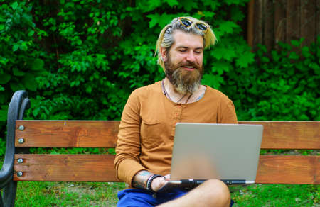 Smiling man working on laptop outdoors. Businessman with notebook at park. Freelance. Study and work online.