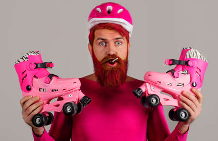 Man in Sport helmet with roller skates and lollipop. Bearded man with roller-skates. Vacation. Healthy lifestyle.