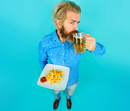 Man with French fries, ketchup and glass of beer. Bearded guy with potato fries. Fast food, unhealthy eating, junk-food.