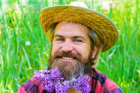 Spring. Smiling Bearded man with flowers in beard. Hipster beard with flowers. Barber shop advertising. Beard style.
