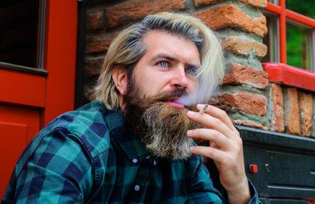 Stylish bearded man with cigarette. Smoking hipster. Cigarette smoke. Male smoke cigarette. Stok Fotoğraf - 166634230
