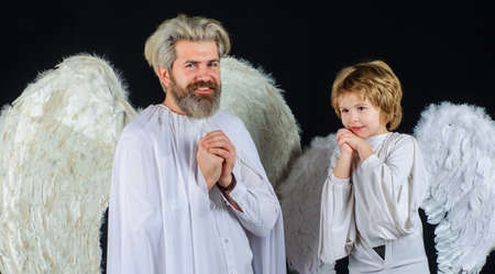 Father and son in angel costumes. Valentines day. Happy family with white wings. 版權商用圖片