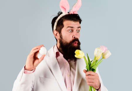 Easter celebration concept. Surprised bearded man in suit with egg and flowers. Eggs hunt.