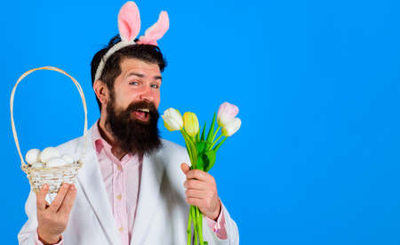 Happy Easter. Smiling business man in suit with basket egg and Spring flowers. Male in bunny ears. Eggs hunt. 版權商用圖片