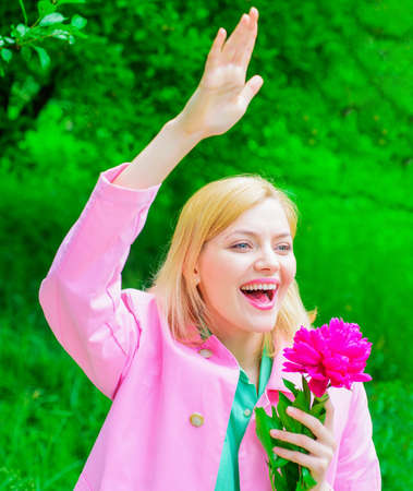 Springtime. Happy woman with peony flower waving hand. Smiling girl welcoming to friends.