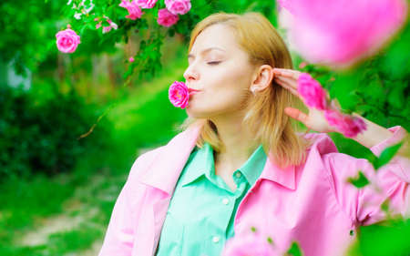 Beautiful girl with spring blooming flowers. Young woman enjoys pink flowers roses. Summertime. Stok Fotoğraf - 166633103