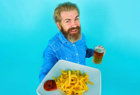 Smiling Man with potato fries and beer. French fries potato. Bearded Male with Potatoes fries and ketchup on plate.