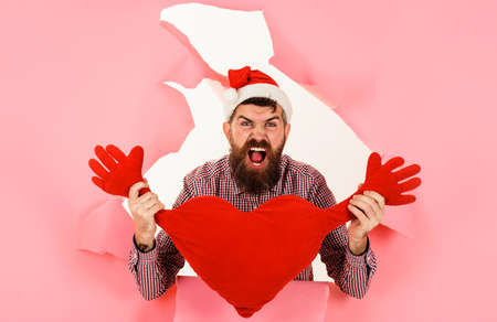 Screaming Santa man with heart shaped pillow. Bearded man in santa hat with red heart cushion.
