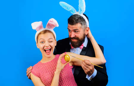 Family celebrate Easter and painting egg. Couple in bunny ears with Easter egg.