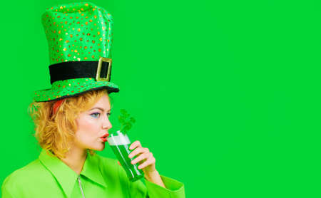 Patricks Day celebration. Beautiful woman in green hat drinking green beer.