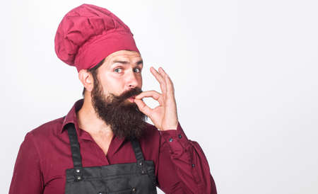 Chef in uniform with perfect sign. Bearded male chef, cook or baker gesturing excellent. Cook with taste approval gesture.