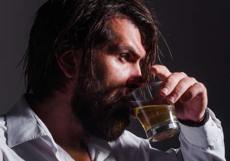 Bearded man tastes whiskey or Brandy. Strong alcohol. Degustation and tasting. Male drinks cognac.