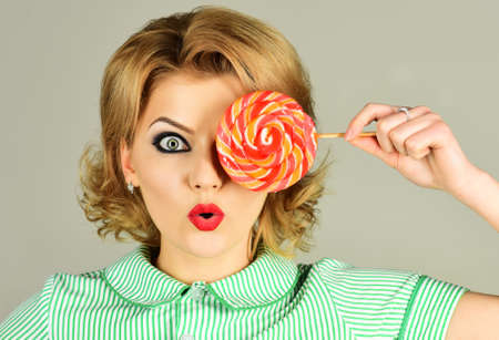 Sexy woman with colourful lollipop. Pinup girl with candy. Sweet food.