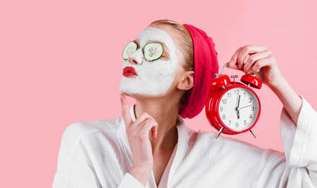 Woman with facial mask on face and alarm clock in hand. Female cosmetic mask. Beauty treatment. Spa therapy. Relax. 版權商用圖片