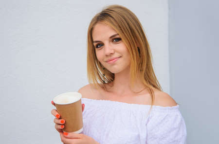 Smiling Girl with coffee or tea in paper cup. Coffee to go. Takeaway. Hot drinks. Espresso, latte, cappuccino. 版權商用圖片
