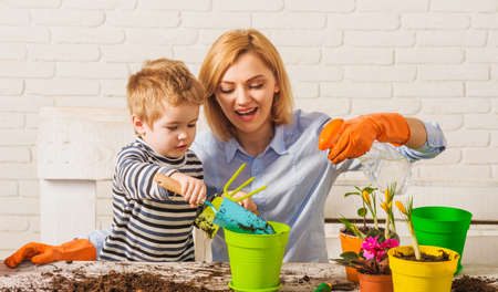 Springtime. Mother with little son planting flower. Family relationships. Care for plants. Gardening.