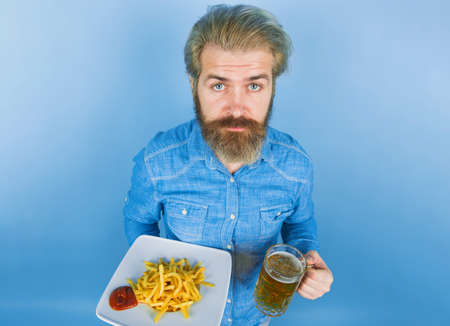 Street food. Fast food. Man with potato fries. Beer. French fries potato. Man drinking beer and eating potato fries. Potatoes frie and ketchup. 版權商用圖片