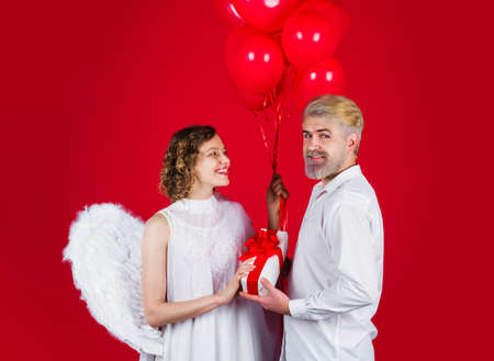 Couple in valentine day. Cupid angel with presents and balloons. Lovely couple. Valentines Day.