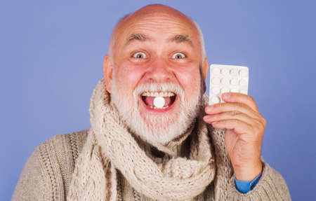 Ill man in scarf with pills from sore throat. Treatment pill. Medicine. Senior man taking pharmaceutical pills. Stok Fotoğraf - 167107646