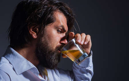 Bearded man drink whiskey or Brandy. Strong alcohol. Degustation and tasting. Male drinks cognac.
