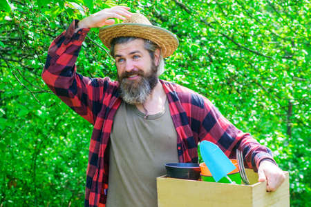 Spring. Bearded man with gardening tools. Happy farmer in spring garden. Gardener with gardening tools.