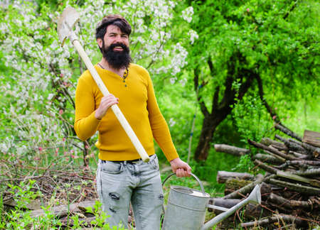 Watering. Gardening. Smiling gardener with watering can and spade. Work in garden. Farm. Spring time.