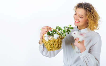 Smiling woman with Easter bunny rabbit and basket eggs. Religion symbol. Egg hunt. Spring holiday. 版權商用圖片