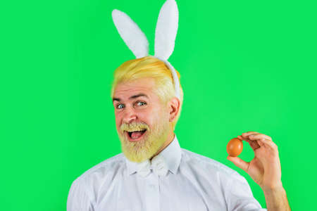 Happy Easter. Bearded man in bunny ears with Easter egg. Rabbit man. Spring time. Eggs hunt.