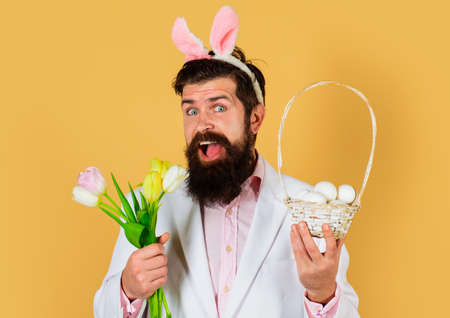 Rabbit man in bunny ears with flowers and basket eggs. Easter celebration concept. Bearded man in suit with Spring flower. 版權商用圖片