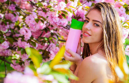 Nature herbal cosmetic for hair. Beautiful woman with shampoo or conditioner. Woman with cosmetics for hair.