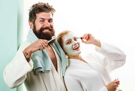 Morning treatments. Couple In bathroom. Husband and wife. Husband with tooth brush, Wife with Cosmetic facial mask. 版權商用圖片