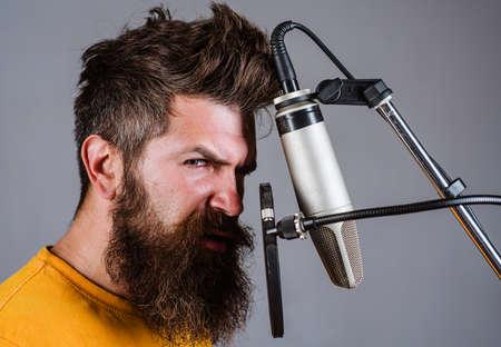 Man singing with microphone in studio. Bearded man in karaoke 版權商用圖片