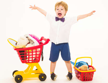 Happy little boy with shopping cart and basket. Child plays in shop. Shopping, discount, sale concept