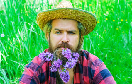 Handsome bearded man with flowers in beard. Man with decorated beard.