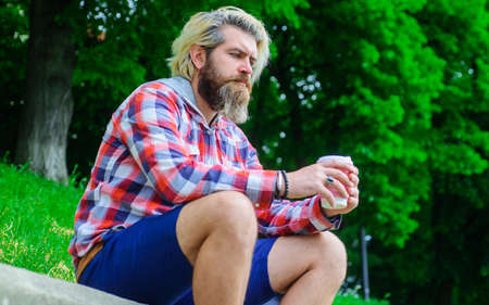 Takeaway coffee. Thoughtful man with coffee outdoor. Bearded man with paper coffee cup.