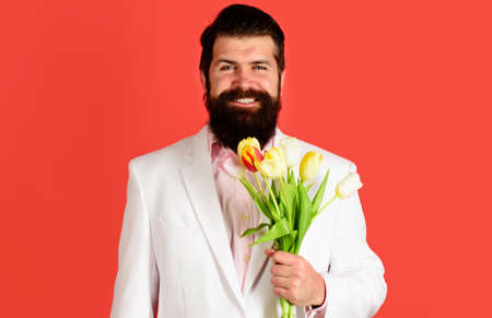Handsome man with Bouquet of tulips. Businessman with flowers for birthday. Valentines Day. Womens Day.