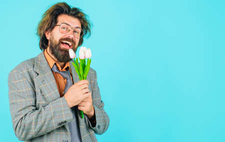 Businessman with bouquet of tulips for birthday. Handsome man with flowers. Smiling man with bouquet of flowers. Copy space.