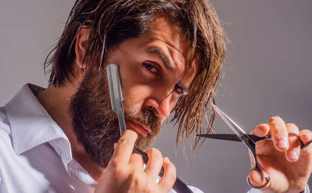 Barbershop. Bearded man with razor and scissors. Salon for men. Handsome man with barber tools.