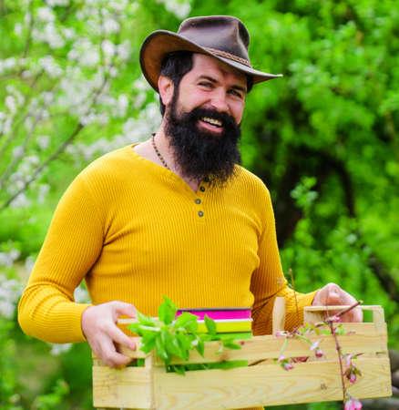 Happy farmer in spring garden. Bearded man with box. Eco farm. Gardener work. 版權商用圖片